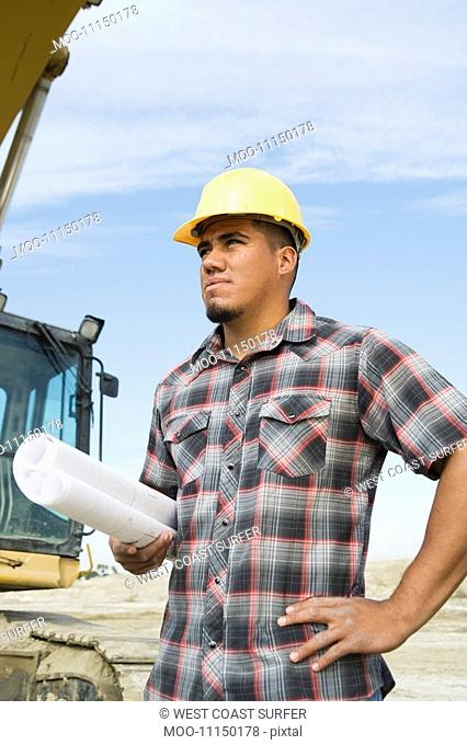 Construction worker holding blueprints on site