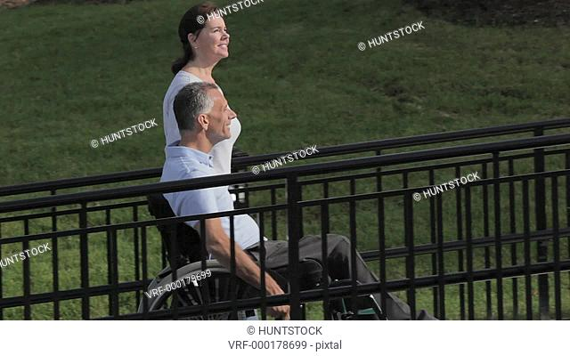 Man with spinal cord injury in a wheelchair using accessible wheelchair ramp with able bodied wife