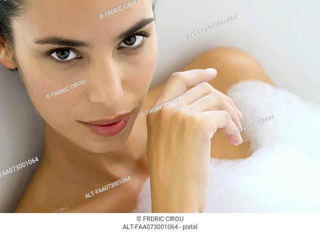 Woman soaking in bubble bath, portrait