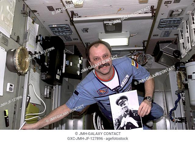 Yury V. Usachev of Rosaviakosmos, Expedition Two mission commander, holds a photograph of Yuri Gagarin in the Zvezda Service Module in commemoration of the...