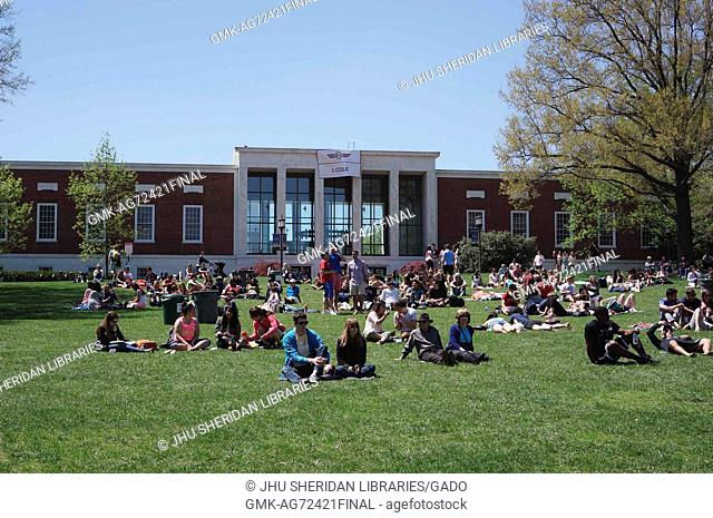 College students and members of the Johns Hopkins and Baltimore communities sit on the beach, a large grassy area in front of the Milton S
