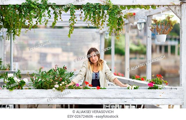 Portrait of a pretty young woman in a vintage setting. Framing of the pure white paint wooden structures with ivy and flowers. Shallow depth of field