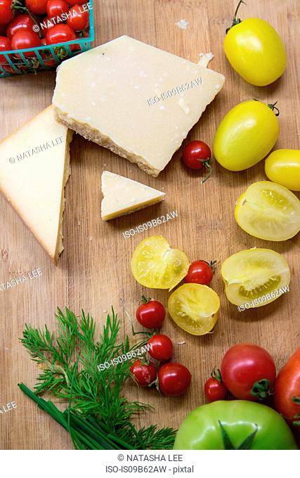 Overhead view of heirloom tomatoes, cheese and dill on chopping board