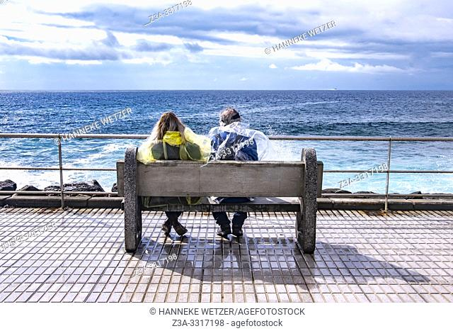 Two persons wearing a poncho looking over the ocean on a bench in Agaeta, Gran Canaria