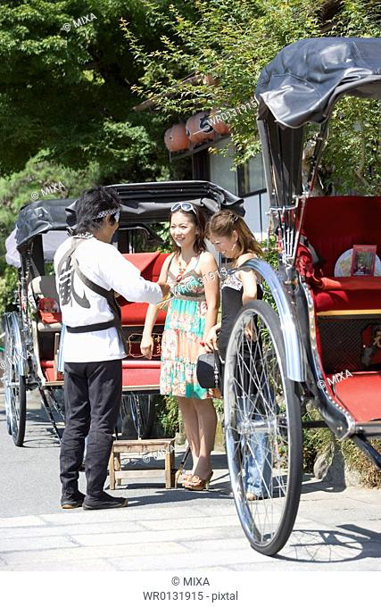 Two young women talking with rickshaw driver