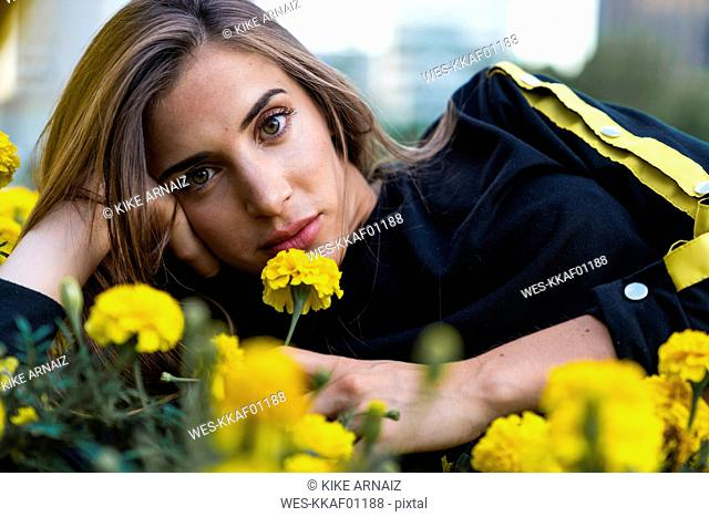 Portrait of attractive young woman lying in flower meadow