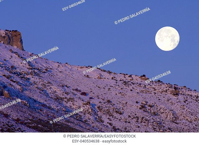 snowy landscape at sunrise with moon in mountains, Saragossa, Aragon, Spain