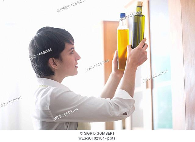 Young woman collating different sorts of cooking oil