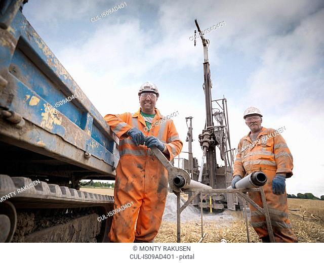 Portrait of drilling rig workers in hard hats and workwear