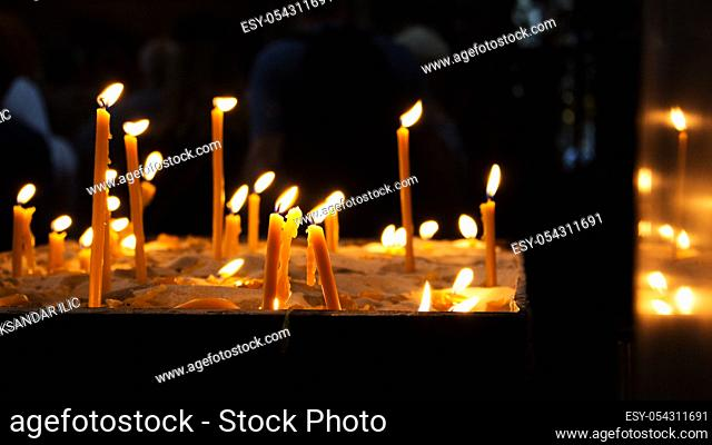 Candles Burning in a Church and Reflecting out of Wall