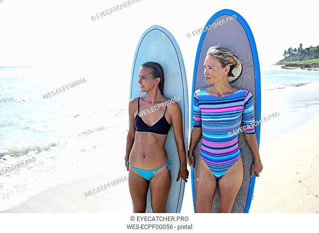 Two women on the beach with surfboards