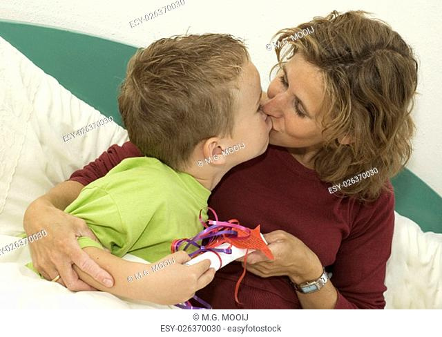 Boy giving his Mothers Day present to his mother. Mother is kissing the boy