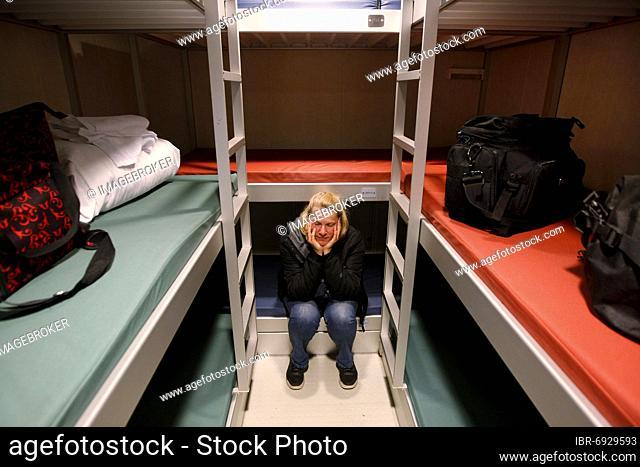 Denmark and Färör ferry Norröna, Smyril Line ship, cabin, woman between bunk beds, Seyðisfjörður, Iceland, Europe