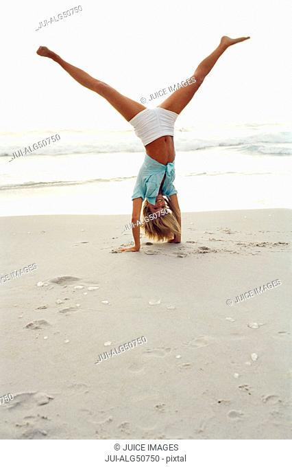 Young woman doing handstand on the beach