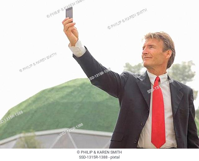 Italy, Piedmont, businessman taking picture with cell phone outside green dome