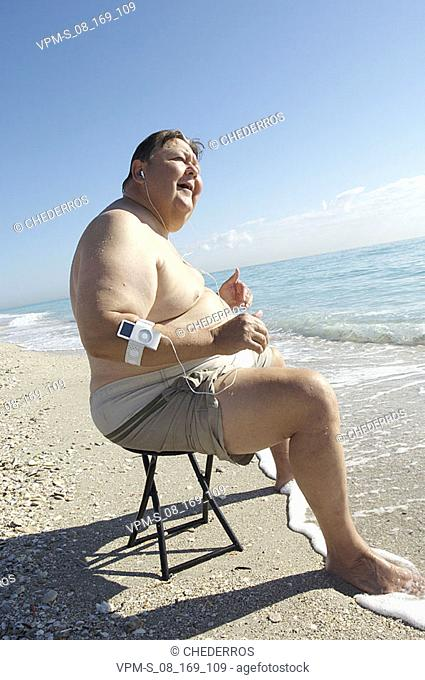 Side profile of a mature man listening to an MP3 player on the beach