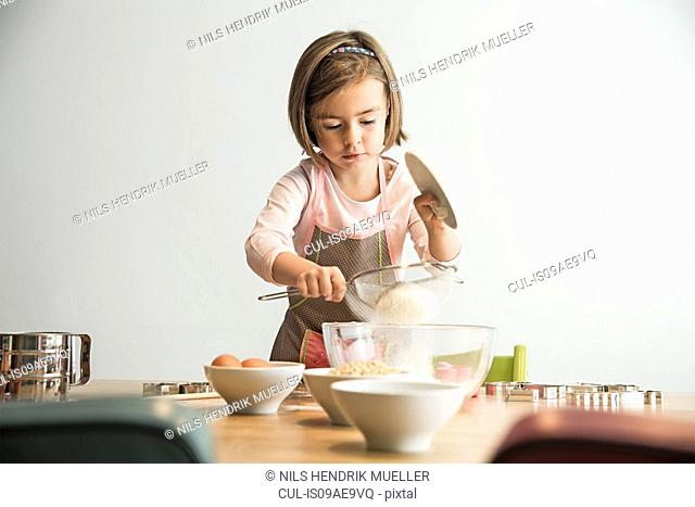 Girl sieving flour into mixing bowl