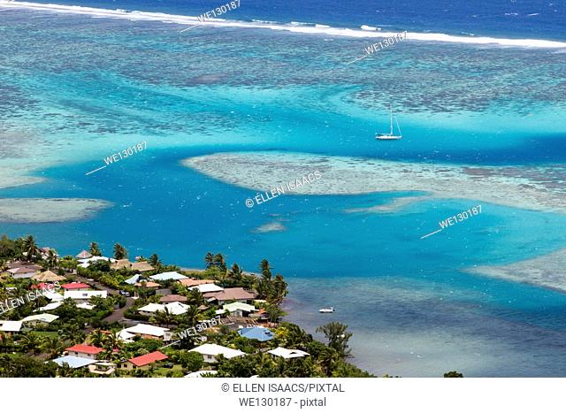 Sailboat anchored in a coral reef off the coast of Moorea with tropical houses on shore