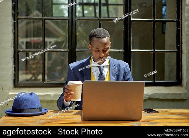 Stylish young businessman wearing old-fashioned suit using laptop at an outdoor cafe