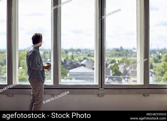 Senior man looking out of window in a loft flat
