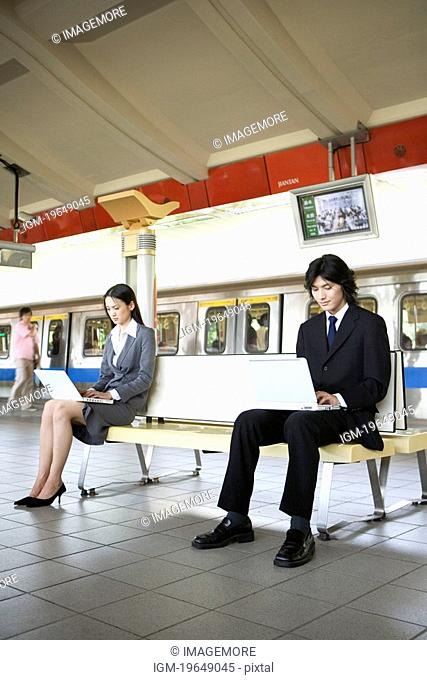 Businessman and businesswoman sitting on bench of platform, using laptops