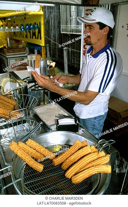 A man making churros,sweet doughnuts with dulce de leche,boiled condensed milk,at a stall