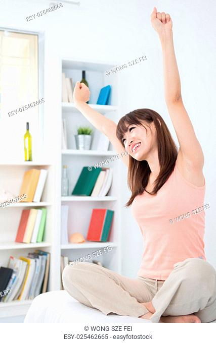 Portrait of Asian girl woke up and stretching arms in the morning. Young woman indoors living lifestyle at home