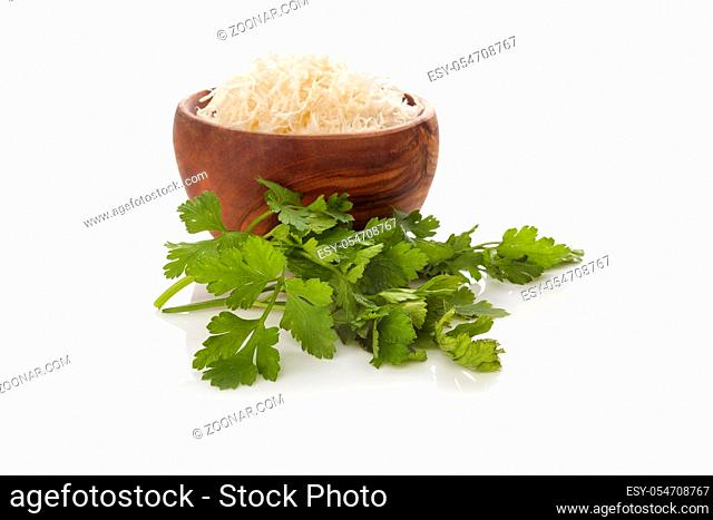 Fresh grated horseradish with parsley in bowl isolated on white background