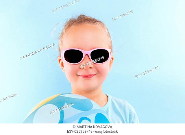Summer. Adorable beautiful girl with ball and sunglasses against blue background. Summer background