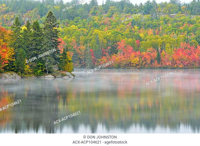 Autumn colour reflected in misty St. Pothier Lake, Greater Sudbury, Ontario, Canada
