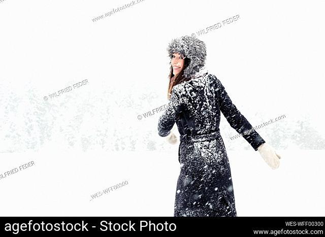 Portrait of happy young woman having fun in winter landscape
