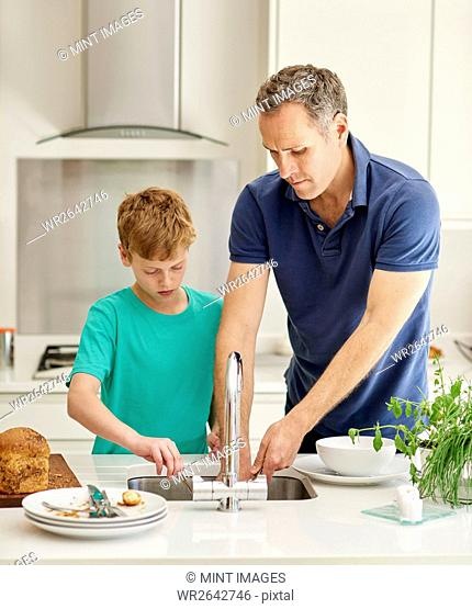 A family home. A man and a young boy in the kitchen side by side doing the dishes