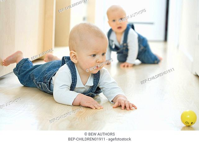 Baby twins playing with yellow ball
