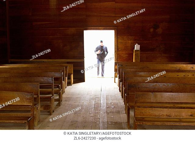 Man with a hat looking like a ghost entering a old church in Cades Cove, Great Smoky Mountains, Tennessee, a vacation destination