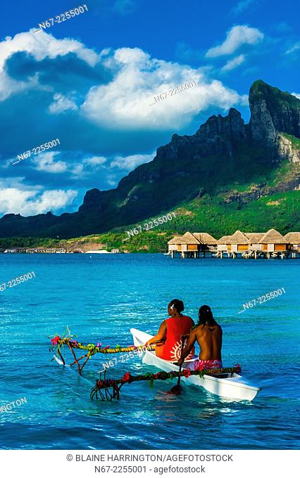 Polynesian couple in an outrigger canoe in the lagoon, Four Seasons Resort Bora Bora, French Polynesia