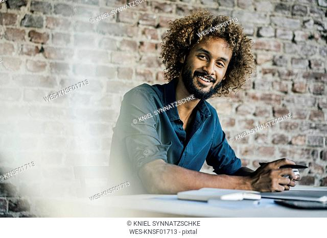 Portrait of smiling young man at desk