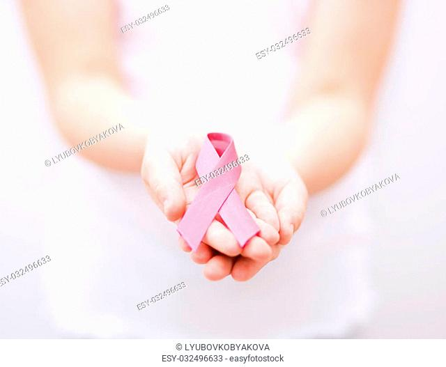healthcare and medicine concept - girl hands holding pink breast cancer awareness ribbon