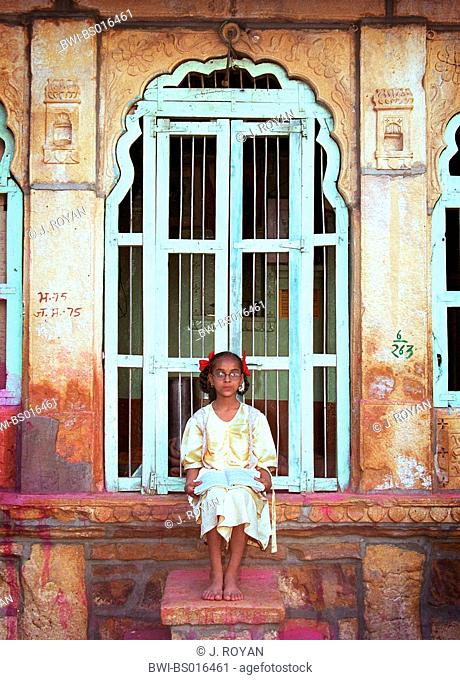 unsmiling Indian girl with queues sitting in front of a front door with a book on the lap, India, Rajasthan, Jaisalmer