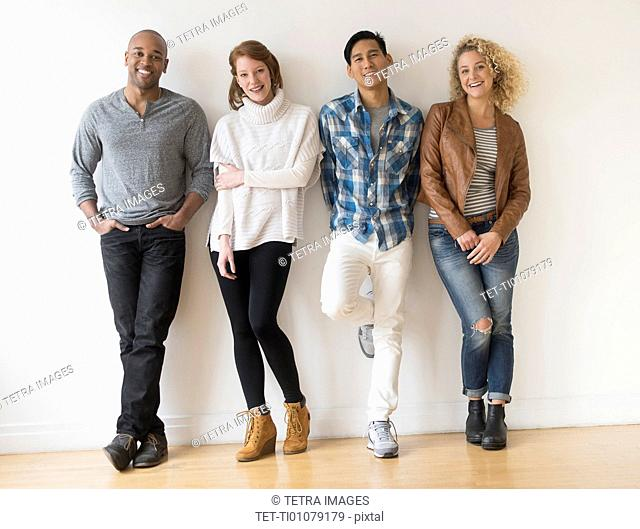 Group of friends standing in front of white wall