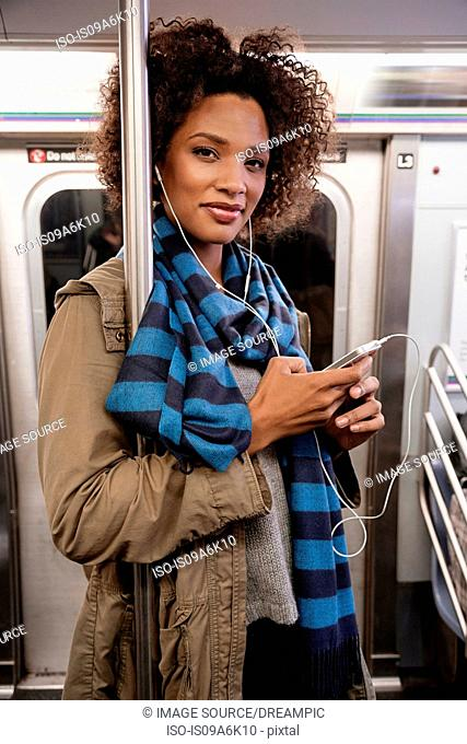 Woman listening to earphones on subway