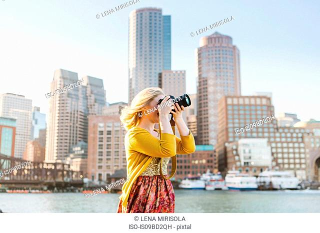 Young female photographer photographing from quayside, Boston, Massachusetts, USA