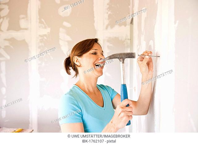 Smiling woman driving a nail into a wall with a hammer