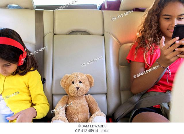 Sisters with teddy bear using smart phone and digital tablet, riding in back seat of car