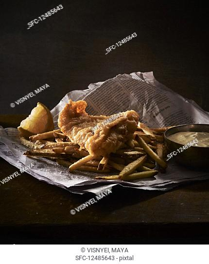 Fried fish with french fies and lemon on newspaper