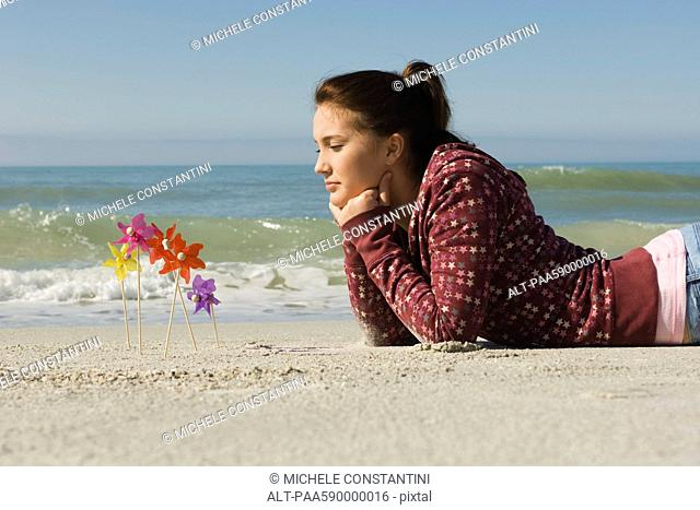 Preteen girl lying on stomach on beach, contemplatively looking at pinwheels stuck in the sand