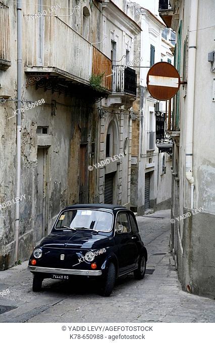 Old car driving at a narrow street in Ragusa Ibla, Ragusa, Sicily