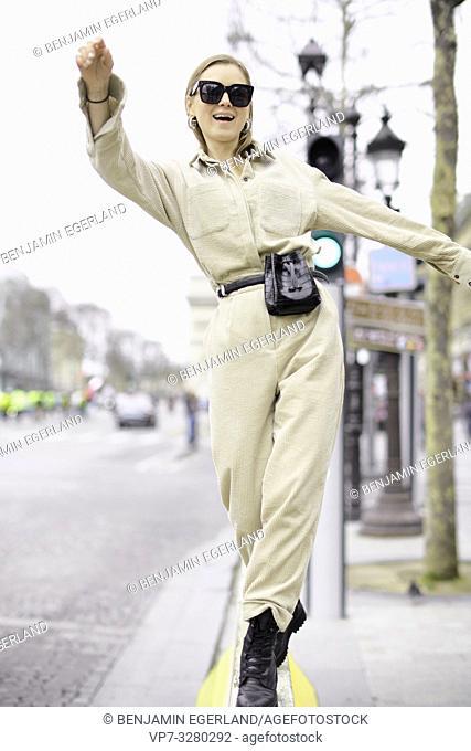 fashionable woman balancing at street during women's fashion week, in Paris, France