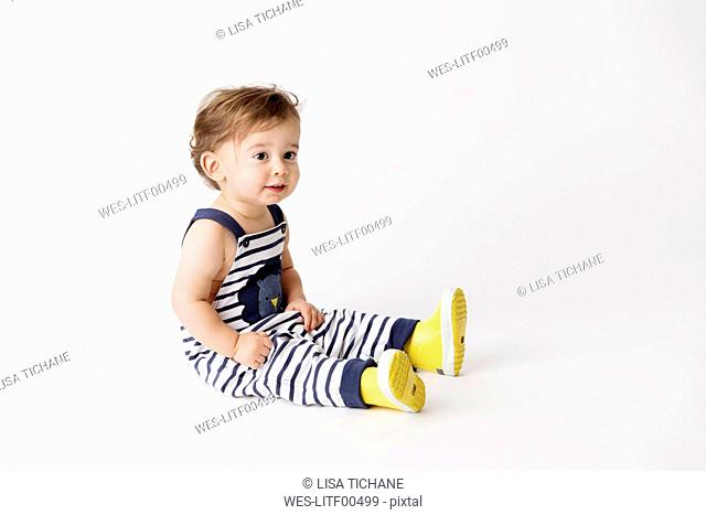 Toddler wearing striped dungarees and yellow rain boots sitting in front of white background