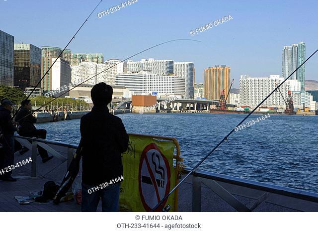 People fishing at the waterfront promenade of Tsim Sha Tsui East, Hong Kong