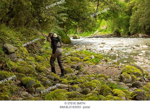 Caucasian woman walking in remote river